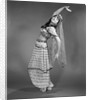 1960s woman in belly-dancer costume stretching back with arms out looking at camera by Corbis