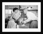 1950s housewife in kitchen having husband taste food on stove by Corbis