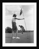 1970s couple playing golf man putting woman holding flag by Corbis