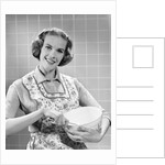 1950s smiling woman wearing apron in kitchen holding mixing bowl and spoon looking at camera by Corbis