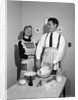 1950s satisfied amused smiling couple husband wife in kitchen cooking together by Corbis