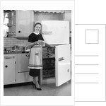 1950s smiling woman housewife in kitchen taking frozen food out of refrigerator freezer by Corbis