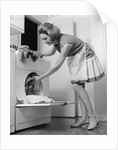1970s woman removing laundry from dryer by Corbis