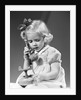 1940s little blond girl talking on toy telephone by Corbis