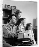 1960s happy family looking at slides on slide projector by Corbis