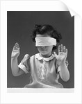 1940s child wearing blind fold with hands up in the air by Corbis