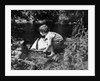 1920s boy putting toy sailboat into stream by Corbis