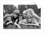 1970s 1980s group of six boys & girls gathered together on large playground tire by Corbis