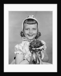 1950s child holding flowers smiling looking at camera by Corbis