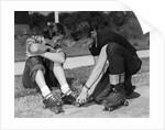1950s teen boy helping girl put on metal roller skates sitting on sidewalk by Corbis