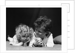 1930s two children brother and sister lying on couch by Corbis
