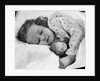 1950s child little girl sleeping in bed with doll by Corbis