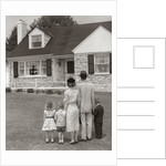 1950s family of five with backs to camera on lawn looking at fieldstone house by Corbis