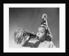 1950s girl wearing party hat blowing into noise maker looking at camera by Corbis