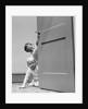 1940s children boy and girl in pajamas peeking around door by Corbis