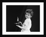 1940s child little girl holding candle looking at camera by Corbis