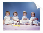 1950s 1960s portrait of quadruplets 4 red haired girls wearing dresses sitting in a row by Corbis