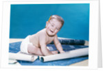 1960s baby eyes closed funny facial expression crawling on rolling out blueprints by Corbis