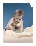 1960s baby reading phone book yellow pages with telephone receiver on shoulder by Corbis
