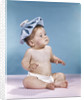 1960s baby sitting with ice pack on top of head by Corbis