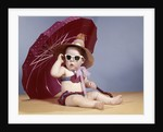1960s baby girl wearing two piece bikini and straw hat sunglasses sitting by red beach umbrella by Corbis