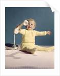 1960s baby holding telephone head set by Corbis