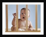 1960s baby in crib or playpen looking through bars alarmed expression by Corbis