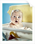 1960s baby in bath looking up by Corbis