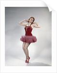 1960s teen girl woman red velvet costume pink net tutu fishnet stockings dance pose en pointe by Corbis