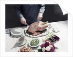 1950s male hands about to carve thanksgiving turkey table setting plates gravy rolls olives crudities by Corbis