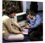 1980s couple by christmas tree reading instructions for an apple iii computer by Corbis