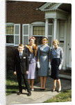 1950s mother with teenage girls & younger son dressed up posing in front of house by Corbis