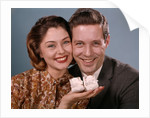 1960s smiling couple holding baby shoes looking at camera by Corbis