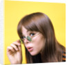 1960s portrait young brunette woman wear granny sunglasses surprised doubtful facial expression yellow background by Corbis