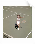 1960s smiling woman playing tennis swinging wood racket to hit ball by Corbis