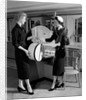 1950s woman in hat stole & gloves taking hatbox from saleswoman by Corbis