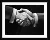 1930s close-up of businessmen's hands in handshake against dark background by Corbis