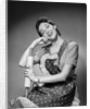 1950s woman housewife wearing apron holding rolling pin looking at camera by Corbis