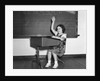 1930s 1940s smiling girl sitting at desk raising her hand by Corbis