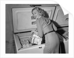 1950s blond woman lifting wire basket food items from a deep freezer looking at camera over her shoulder by Corbis