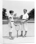 1920s 1930s two boys tennis match holding rackets measuring net height by Corbis
