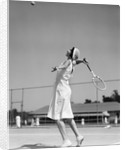 1930s woman playing tennis about to hit ball with racket by Corbis