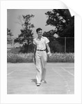 1930s man walking across tennis court holding tennis racket & balls by Corbis