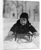 1930s young smiling boy on sled in snow looking at camera by Corbis