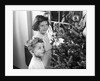 1950s boy girl wearing pajamas smiling up at christmas tree decorations by window by Corbis