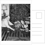 Father with daughter and son in front of Christmas tree, ca. 1950 by Corbis