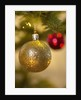 Close-up of a golden hanging Christmas bauble on blurred tree by Corbis
