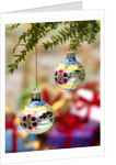 Close-up of decorated hanging baubles against blurred gifts in the background by Corbis