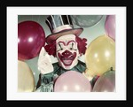 1950s Circus Clown Portrait Smiling Amid Balloons Pointing Up Looking At Camera by Corbis