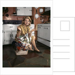 1960s Young Smiling Blond Housewife Sitting On Top Of Laundry Basket Kitchen by Corbis